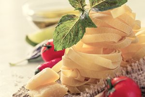 Pasta and ingredients on rustic background