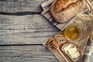 Sliced bread, honey, wheat, rustic wood background