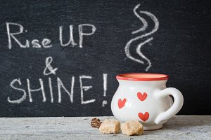 Coffee cup with hearts in front of chalk board
