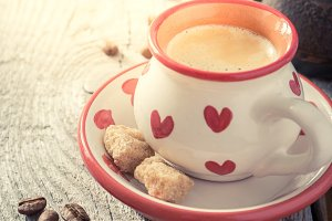 Coffee in white cup with hearts, beans, rustic wood background
