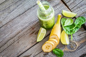 Green smoothie on rustic wood background