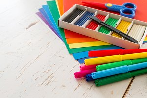 Selection of child stationery on white wood background