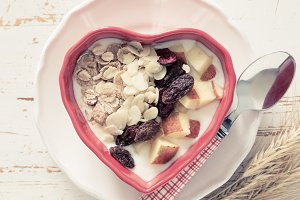 Muesli in heart shaped bowl, white wood background