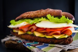 Large sandwich with avocado ham chese and egg, dark background