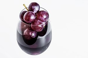 Grapes berries in a glass of wine