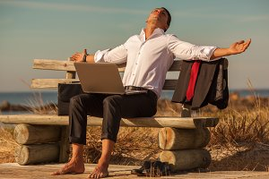 Businessman resting on the coast