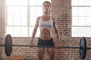 Fit young female athlete lifting