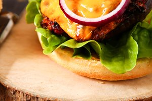 Delicious fresh homemade burger on dark serving board with spicy tomato sauce herbs over dark wooden background.