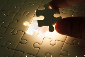 Hand insert missing jigsaw puzzle