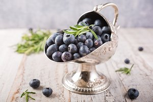 Fresh blueberries in vintage metal sugar bowl