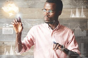 Attractive African businessman wearing glasses navigating futuristic interface looking at the screen with concentrated and serious expression while working on a project, making graphics and diagrams