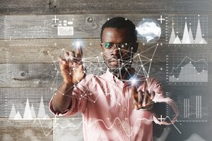 Visual effect. Worldwide interface. Concentrated African American programmer working on a project, making graphics and diagrams, touching futuristic screen interface . Selective focus on the face