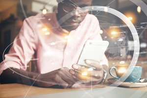 Double exposure. Visual effects. Futuristic technology and connection. Young African freelancer or office worker checking email or reading news on the Internet using smart phone. Selective focus