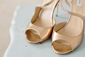 Gold Wedding Shoes on a rustic table