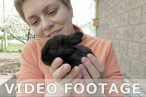 Girl holds and pets little baby black rabbit