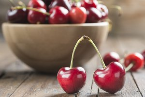 Wooden bowl of cherries on the table