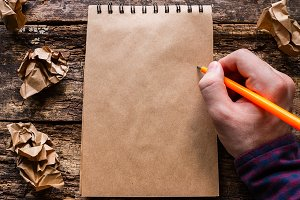 man writes in a notebook