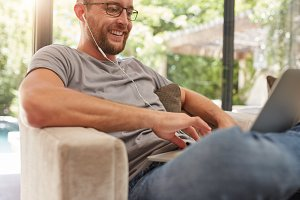 Man with laptop relaxing on a sofa