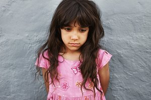 Little girl standing looking upset