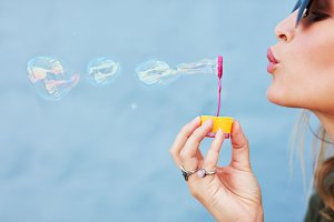 Young female blowing soap bubbles