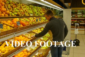Man choose orange in the hypermarket