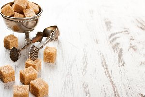 Brown sugar cubes and metal sugat tongs