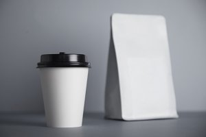 White paper cups isolated on gray mockup set