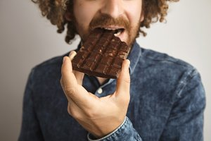 Happy curly man eats chocolate