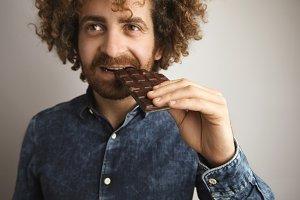 Happy curly man eats chocolate