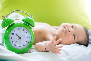 Kid with a large alarm clock