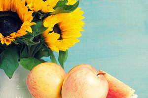 Sunflowers bouquet in white vase with apples