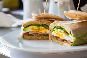 Sandwich with egg, ham, avocado in restaurant