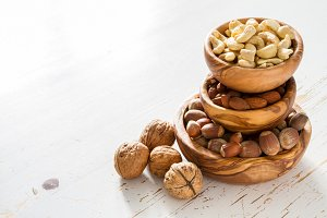 Selection of nuts on white wood background