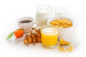 Breakfast concept - croissant, juice, coffe and cereal