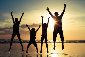 Happy family jumping on the beach.