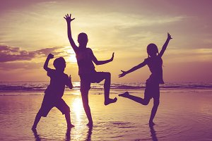 Happy children dancing on beach.