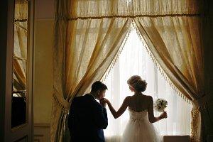 bride and groom standing in front of window