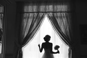 beautiful bride in a wedding dress, by window.