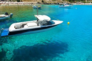 floating in the water Boat on background beach and bathing people in Bay of Lindos, Rhodes Greece