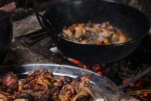 Frying rabbit meat over hot coals.