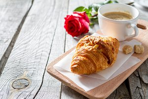 Delicious fresh croissants with coffee and rose