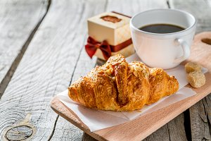 Delicious fresh croissants with coffee and present