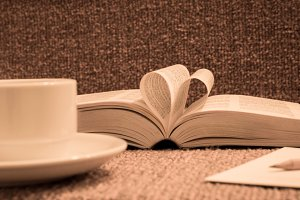 book rolled in heart with coffee
