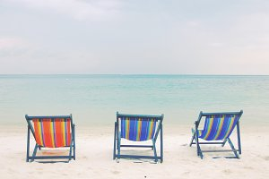 Three deck chairs on beach