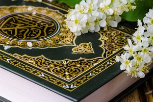 Quran - holly book of islam with spring flowers and blue scarf on wooden background. Selective focus on book
