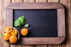 Fresh ripe apricots in wood bowl on vintage slate chalk board background. Selective focus. Background with place for some text. Top view