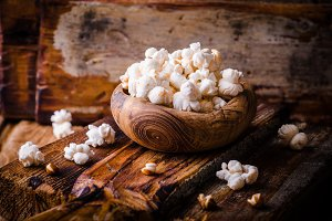 Wooden bowl full of sweet popcorn in wooden vintage bowl on rustic table. Vintage style. Selective focus