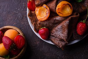 Stack of chocolate crepes decorated with strawberry and grilled apricots on dark slate background. Selective focus. Top view. Background with place for some text