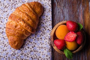 Croissant with strawberry and apricots on over white linen tablecloth.. Breakfast concept. Selective focus. Top view