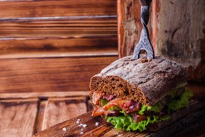 Burger sandwich with lettuce, roasted bacon on dark wood cutting board. Selective focus